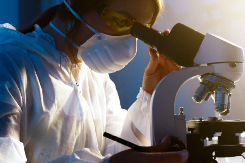Doctor looking through microscope