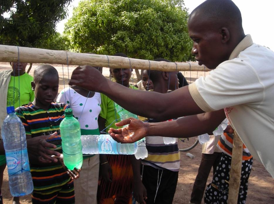 Rachel's counterpart, Narcisse, demonstrating how to use the new handwashing station at the school